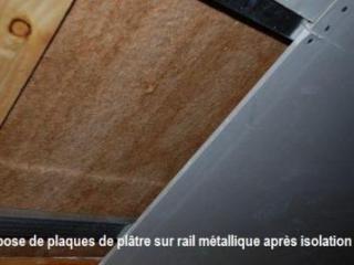 Pose de plaques de plâtre sur les panneaux pour terminer l'isolation des combles