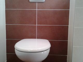 Installation d'un wc suspendu dans le coin d'une grande salle de bain rénovée