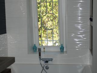 Pose d'une baignoire avec carrelage mural blanc à relief horizontaux