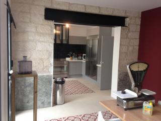 Mur en pierre ouvert avec vue sur la cuisine rénovée