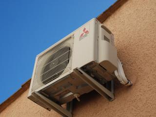 Installation d'une climatisation sur la façade d'une maison du Gard